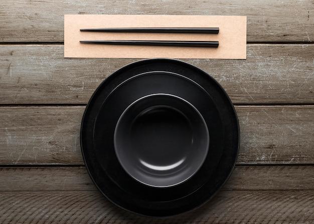 Вид сверху тарелки с палочками и миской