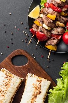 Вид сверху тарелки с вкусным кебабом и салатом
