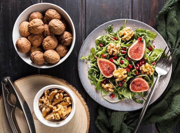 Вид сверху тарелки с инжирным салатом и грецкими орехами