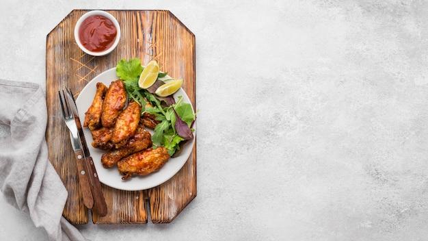 Вид сверху тарелки с жареной курицей и копией пространства
