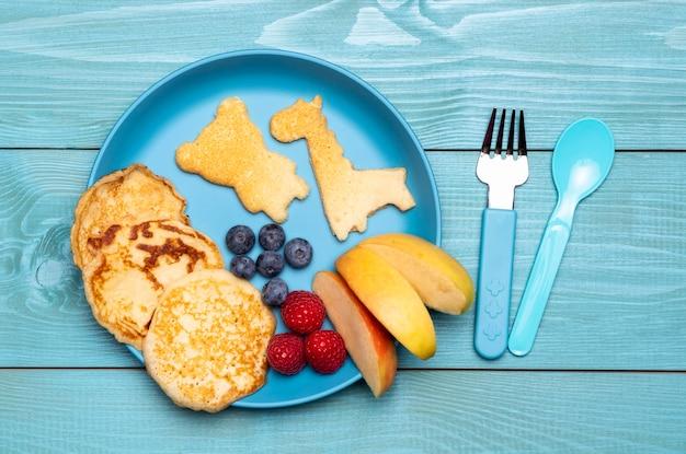 Вид сверху тарелки с фруктами и блинами для детского питания