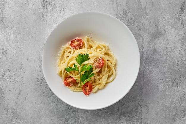 Вид сверху тарелки с лапшой с сыром пармезан и помидорами