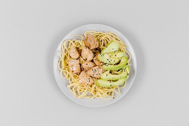 Вид сверху тарелка с макаронами и авокадо