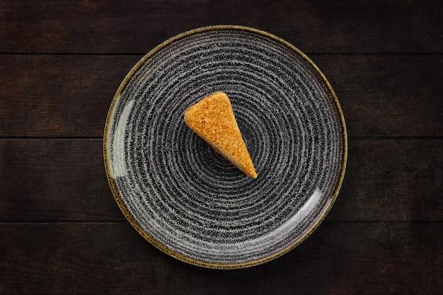 木製の背景に蜂蜜ケーキの部分とプレートの上面図