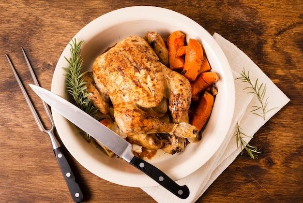 Вид сверху на тарелку с жареной курицей на день благодарения и столовыми приборами