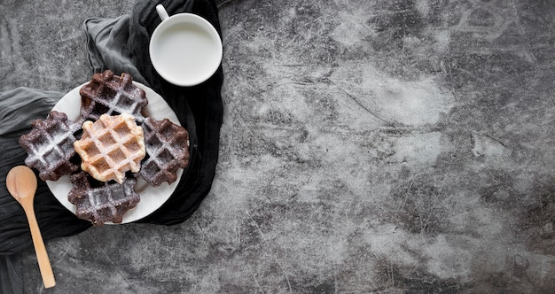Вид сверху тарелки с вафлями, покрытыми сахарной пудрой