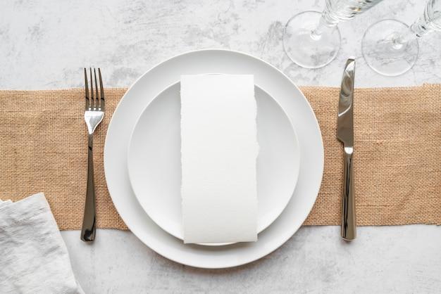 Вид сверху тарелок на мешковину со столовыми приборами