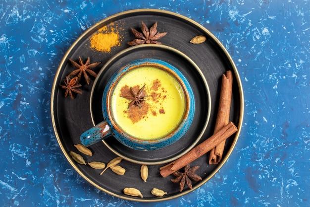 青の背景に伝統的なインドのアーユルヴェーダの黄金のターメリックミルクと食材のカップとプレートの平面図です。