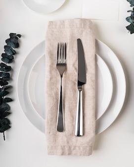 Вид сверху тарелок со столовыми приборами и тканью
