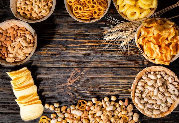 小麦の近くにピスタチオ、ナッツ、その他のおいしいビールスナックが入ったプレートの上面図。暗い木製の机の中央にコピースペースがある散らばったチップス。食品および飲料の概念