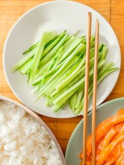 Вид сверху на тарелки с нарезанным огурцом, отварным рисом, ломтиками лосося и бамбуковыми палочками для еды.