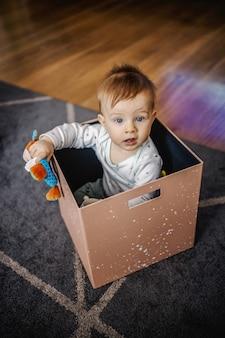 遊び心のある白人の愛らしい小さな金髪の少年がボックスに座っていると彼のお気に入りのおもちゃで遊んでの平面図です。ホームインテリア。