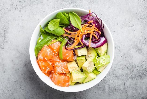 新鮮な生鮭、アボカド、米、ほうれん草、野菜を入れたポークボウルの上面図。素朴な石の背景に伝統的なハワイ料理。健康的で清潔な食事のコンセプト。生の魚のスライスで突く