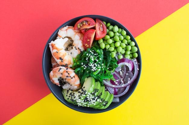 暗いボウルに赤いエビと野菜のポークボウルの上面図