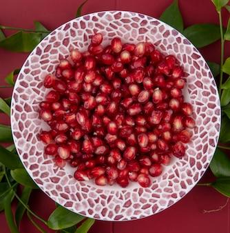Вид сверху ягод граната в миску с листьями на поверхности бордо