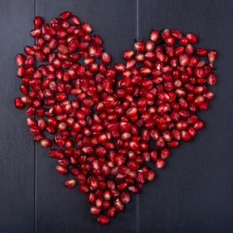 Вид сверху ягод граната на черной поверхности сердца концепции