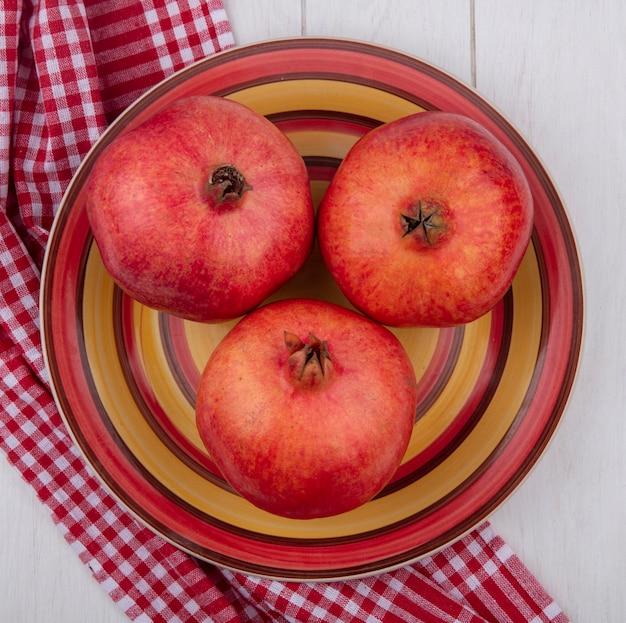 Вид сверху граната на тарелке с красным клетчатым полотенцем на белой поверхности