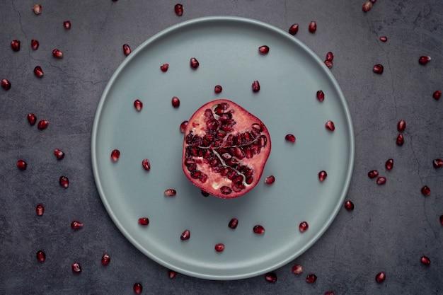 Вид сверху граната на тарелку с семенами