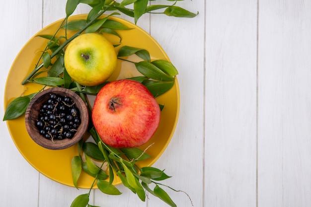 Вид сверху граната с яблоком и черной смородиной с ветвями листьев на белой поверхности желтой пластины
