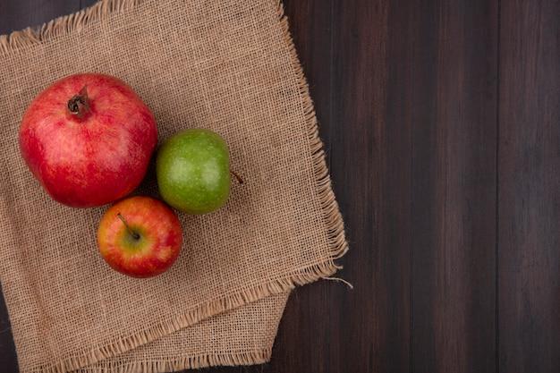 Вид сверху граната с яблоками на бежевой салфетке на деревянной поверхности