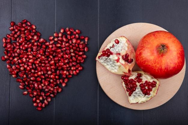 Вид сверху граната с кусочками на разделочной доске и ягоды в форме сердца на черной поверхности