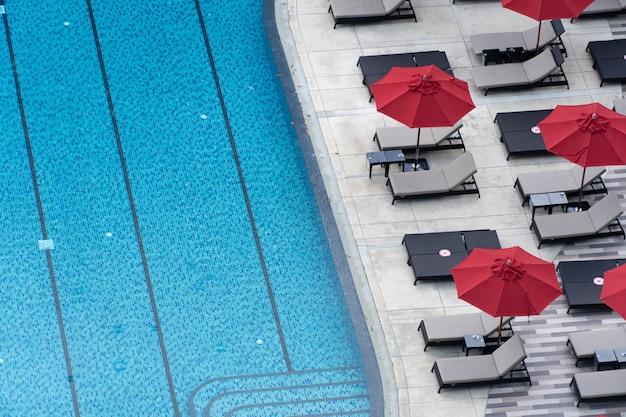 Вид сверху на бассейн в отеле с кушеткой. фон концепция для отдыха и туризма