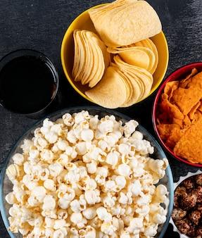 Вид сверху попкорн и чипсы в мисках на черном горизонтальном
