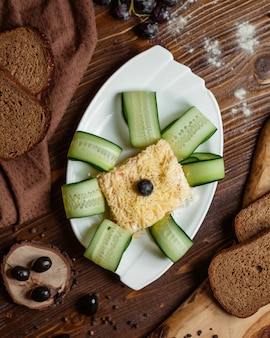 Вид сверху порционного салата мимозы в белом блюде с кусочками огурца