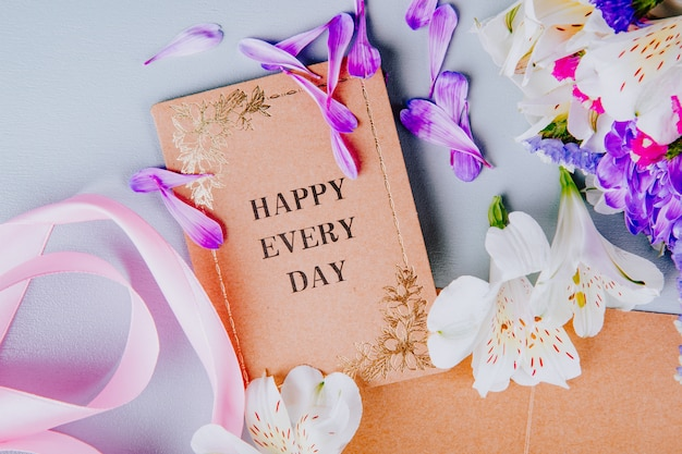 Вид сверху открытки розовой ленточкой и бело-фиолетового цвета статицы и альстромерии на белом фоне