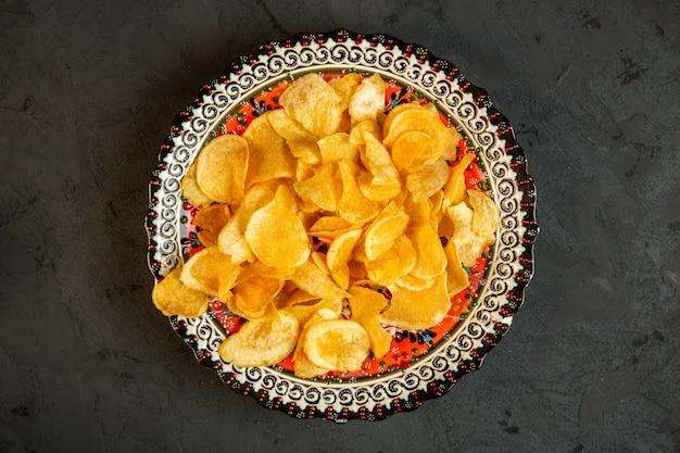 Вид сверху картофельных чипсов в тарелку с восточными принтами на черном