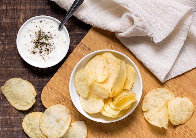 Вид сверху картофельных чипсов в миске с соусом