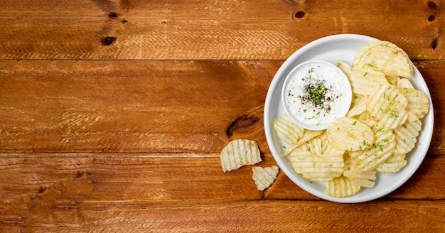 Вид сверху картофельных чипсов на тарелку с соусом и копией пространства