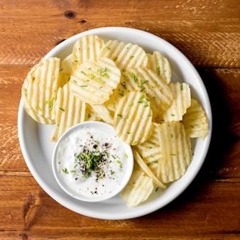 소스와 함께 접시에 감자 칩의 상위 뷰