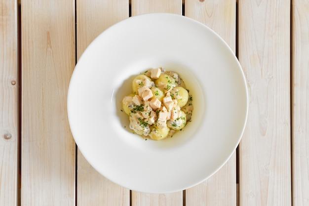 Вид сверху картофельные клецки с вареным куриным мясом в большой тарелке