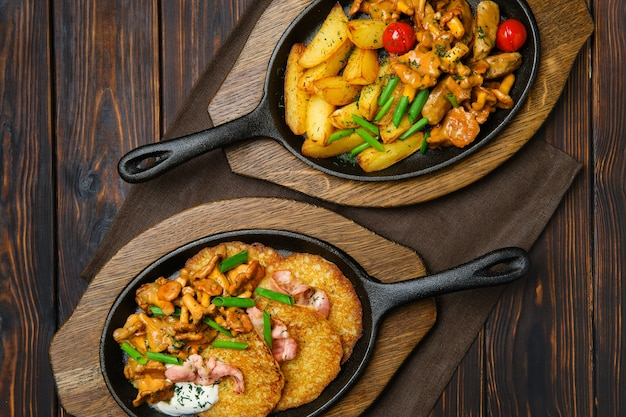 Вид сверху картофельные дольки с лисичками и свининой в чугунной сковороде