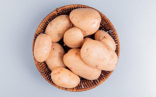 Вид сверху картофеля в корзине на синей поверхности