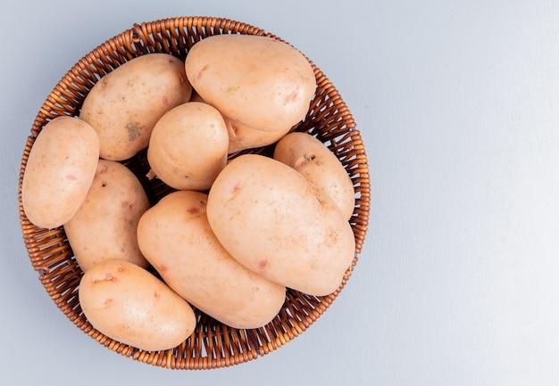 Вид сверху картофеля в корзине на синем с копией пространства
