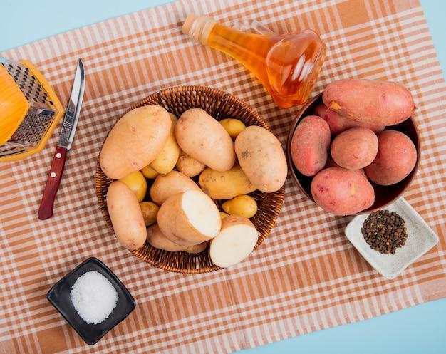 Вид сверху картофеля в мисках с солью черный перец терка нож масло сливочное на клетчатой ткани и синем фоне