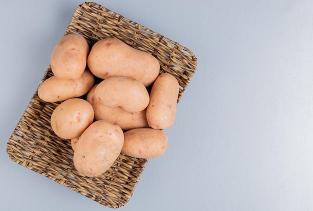 Вид сверху картофеля в тарелку на синей поверхности с копией пространства