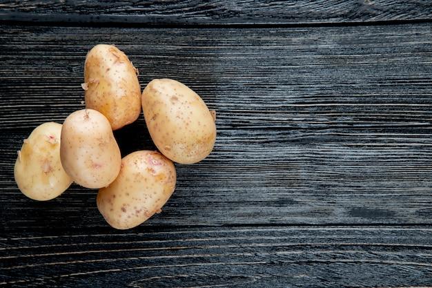Вид сверху картофеля на левой стороне и деревянный фон с копией пространства 2