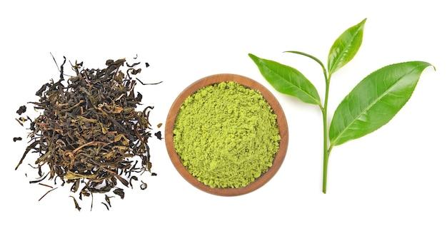 白い背景にある粉緑茶と緑茶の葉のトップビュー
