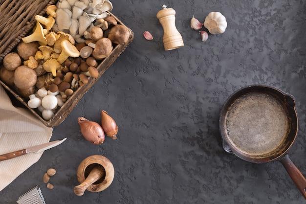 식용 야생 버섯, 음식 사진의 준비 및 튀김의 상위 뷰. 주철 팬에 살구 버섯, 포토 벨로, 표고 버섯을 섞습니다. 향신료, 버터, 파슬리, 양파, 부추, 마늘 요리. 프리미엄 사진