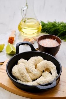 Вид сверху приготовленных для жарки сырых креветок в сырной панировке со специями