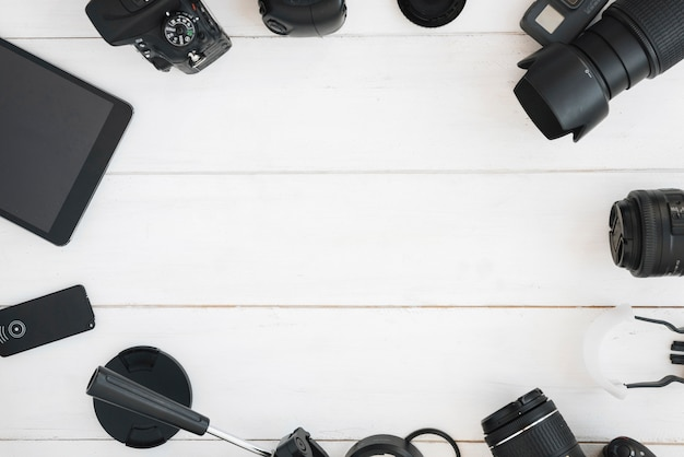 白い木製のテーブルの上のプロの写真アクセサリーのトップビュー