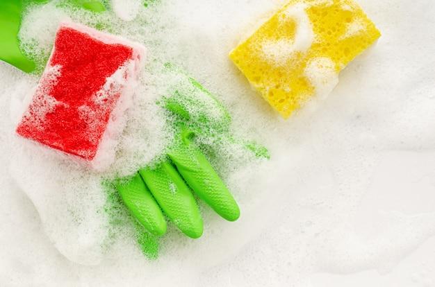 Взгляд сверху защитных зеленых перчаток и губки на мыльной предпосылке. концепция работы по дому. копирование пространства, вид сверху