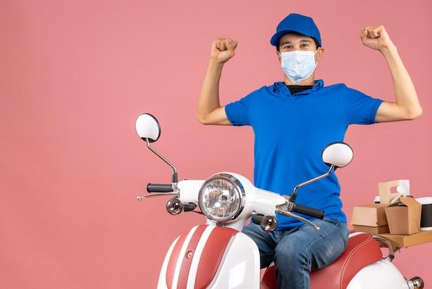 パステル調の桃の背景にスクーターに座っている帽子をかぶった医療用マスクを着た、誇り高い野心的な宅配便のトップビュー