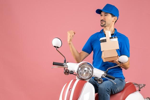 パステル調の桃の背景に注文を保持しているスクーターに座っている帽子をかぶった誇り高い宅配便のトップビュー