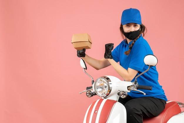 医療用マスクと手袋を着た誇り高い配達員がスクーターに座ってパステル調の桃の背景に注文を配達しているトップビュー