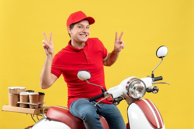 赤いブラウスと帽子を身に着けている誇り高き若い男の上面図黄色の背景に勝利のジェスチャーをする注文を配信します。