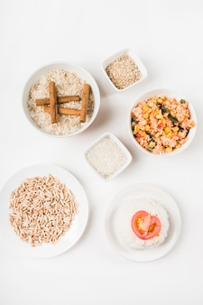 Top view of puffed rice; chinese fried rice and uncooked rice with cinnamon sticks